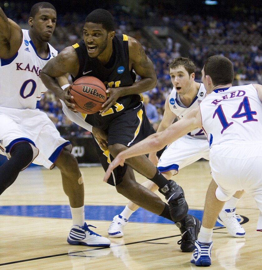 Kansas forward Thomas Robinson (0), Kansas guard Brady Morningstar (12) and Kansas guard Tyrel Reed (14) try to slow VCU forward Jamie Skeen (21) during the Southwest Regional final of the NCAA tournament on March 27, 2011, in San Antonio.