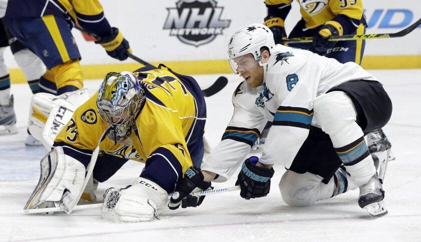 San Jose Sharks center Joe Pavelski (8) tries to take the puck from the grasp of Nashville Predators goalie Pekka Rinne (35), of Finland, in the third period of an NHL hockey game Saturday, Feb. 6, 2016, in Nashville, Tenn. (AP Photo/Mark Humphrey)
