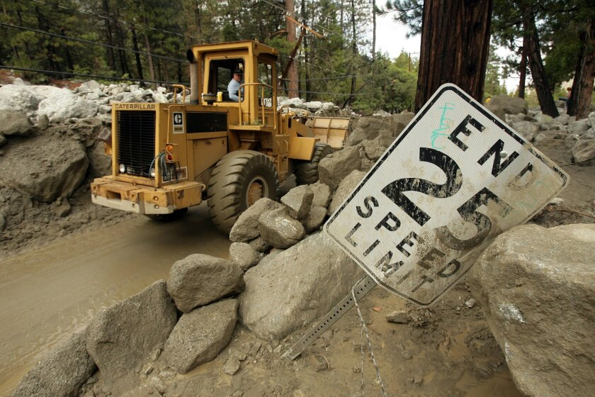 Crews work to remove the debris that washed along Valley of the Falls Dr. on Monday, Aug. 4, 2014 in Forest Falls, Calif. Heavy rains the day before washed dirt and boulders around the small mountain town. (AP Photo/The Press-Enterprise, Stan Lim) MAGS OUT; MANDATORY CREDIT