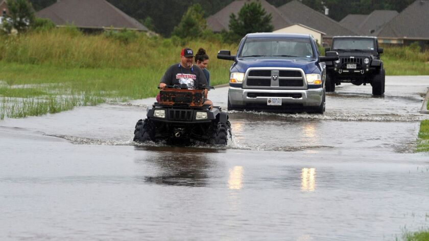 Jason Hendry drives his daughter, Callie, out of their neighborhood on a flooded road in Lumberton, Texas, on Aug. 27, 2017.