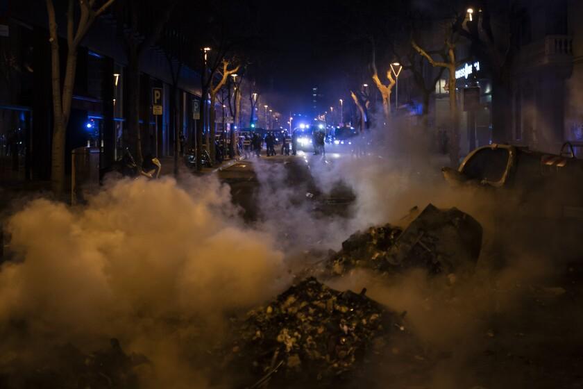 Dos mujeres sentadas contemplan una barricada en llamas erigida por manifestantes durante una protesta