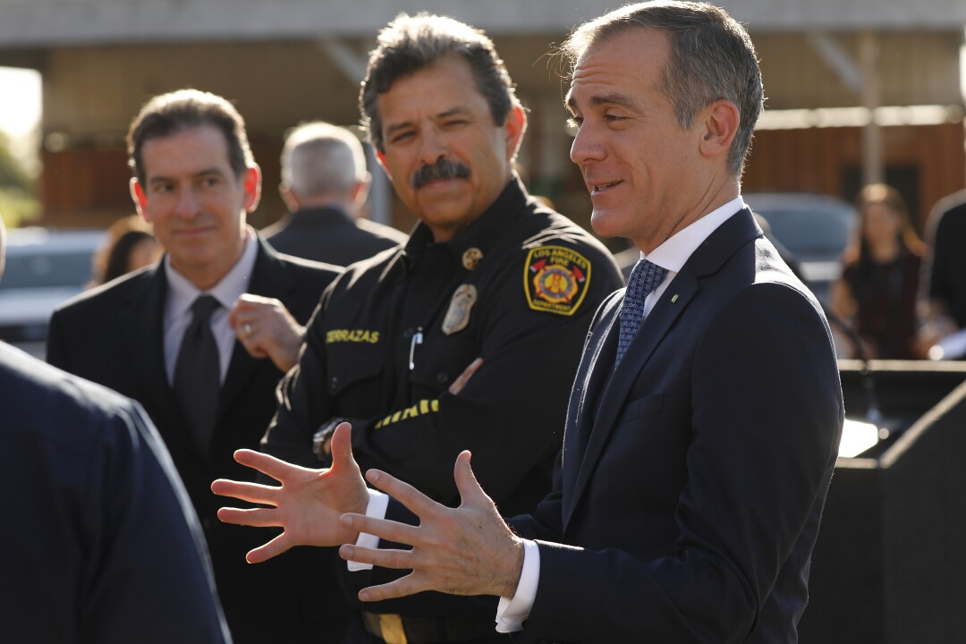 A fire chief in uniform stands between men in suits at a news conference.