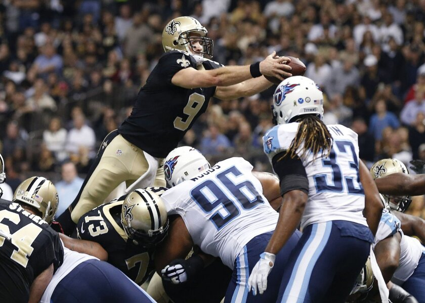 New Orleans Saints quarterback Drew Brees (9) scores a touchdown in the first half of an NFL football game against the Tennessee Titans in New Orleans, Sunday, Nov. 8, 2015. (AP Photo/Butch Dill)
