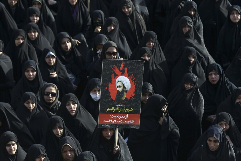 An Iranian woman in Tehran on Monday holds up a poster showing Sheikh Nimr Al-Nimr, a prominent opposition Saudi Shiite cleric who was executed last week by Saudi Arabia.