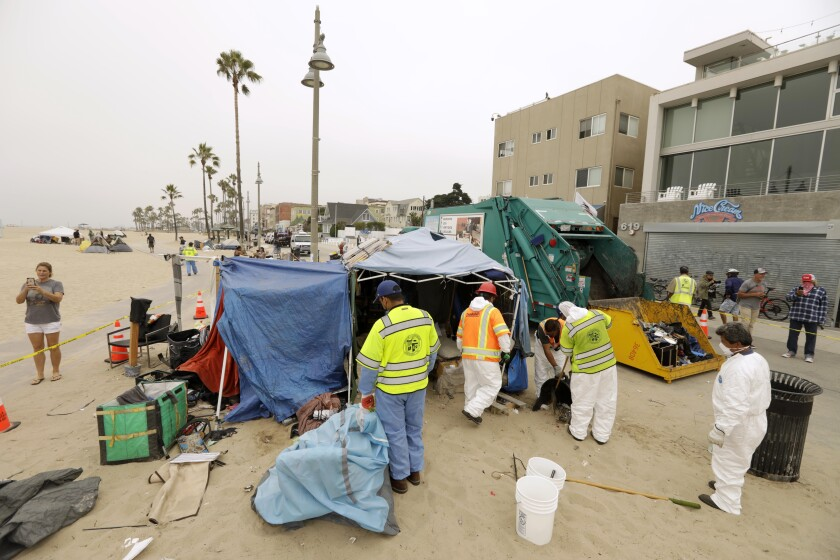 Workers stand outside makeshift tents on the beach with a sanitation truck nearby.