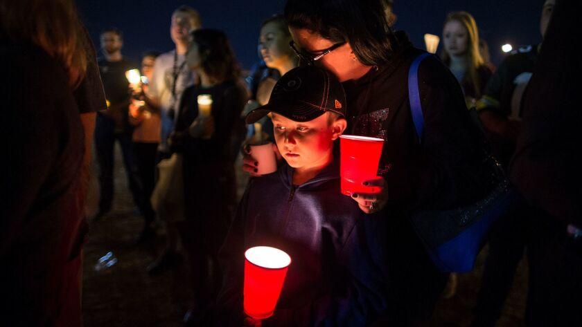 LAS VEGAS, NV - OCTOBER 2, 2017: Keli McDade of Las Vegas leans on her son Ayden during a candle li