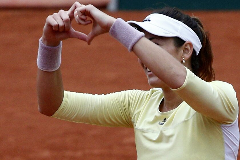 Spain's Garbine Muguruza makes a heart with her fingers after defeating Australia's Samantha Stosur walk back after their semifinal match of the French Open tennis tournament at the Roland Garros stadium, Friday, June 3, 2016 in Paris. Muguruza won 6-2, 6-4. (AP Photo/Christophe Ena)