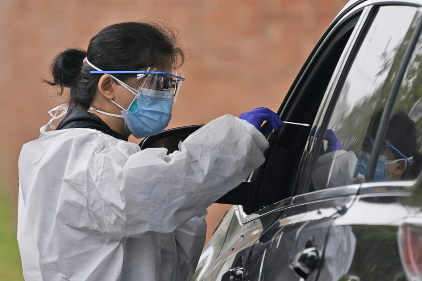 A health worker collects a sample at a drive-through coronavirus testing site
