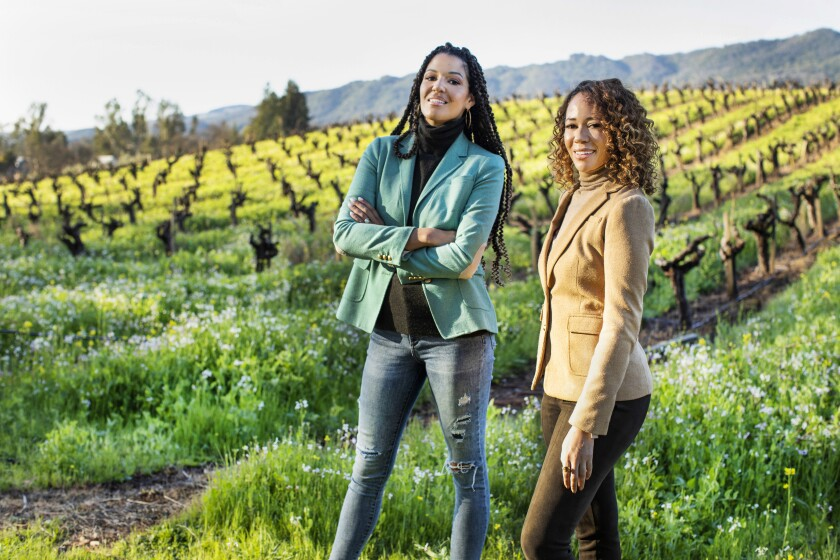 Two women stand and smile in front of a vineyard