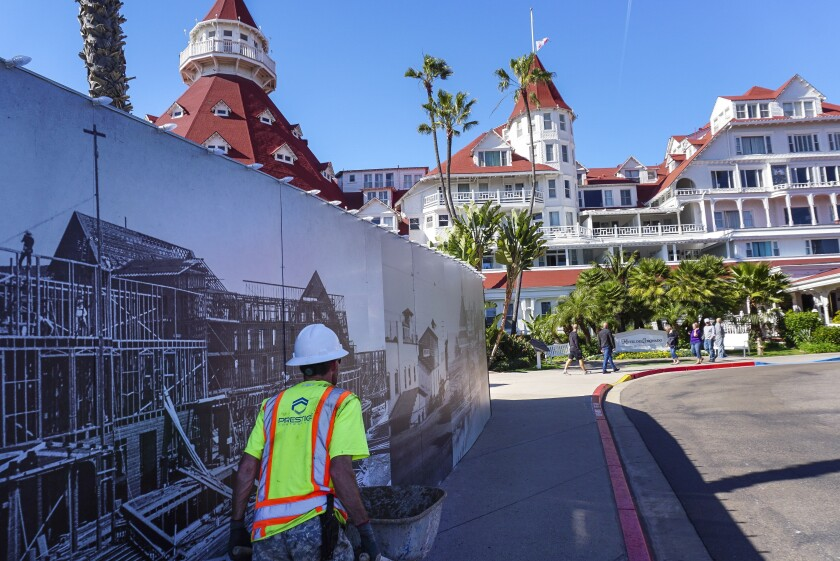 Hayne Palmour IVU-T A construction worker walks past fencing that pictures the original Hotel del Coronado. Renovation work could force as many as 160 layoffs.