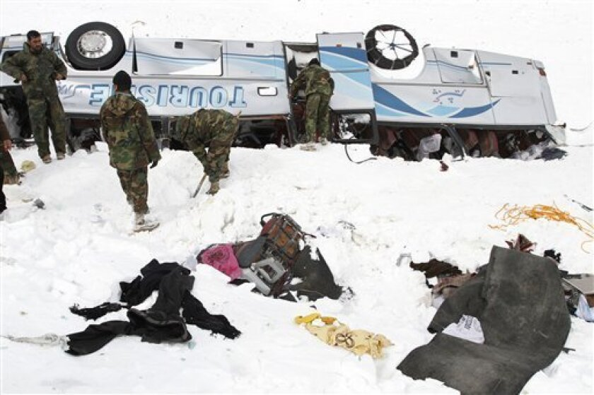 Members of the Afghan army work to uncovered an overturned passenger bus buried in the snow at Salang Pass, some 115 kilometers (71 miles) north of Kabul, Afghanistan, Wednesday, Feb. 10, 2010. The death toll from massive avalanches that blocked the mountain pass north of Kabul soared, as rescuers recovered 157 bodies, while hundreds more remained trapped in their snowbound vehicles, Afghan officials said Wednesday. (AP Photo/Musadeq Sadeq)