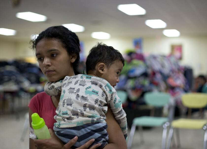 Rose Danubia Maldonado, 18, of Honduras, holds her 14-month-old son, Miguel Yahyr Padilla, as she receives instructions on how to use the bus system at a migrant assistance center at Sacred Heart Catholic Church in McAllen, Texas.