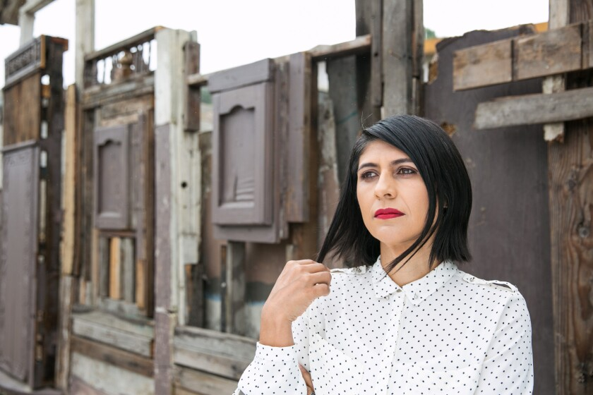 In her work, artist Ingrid Hernandez captures the improvisational nature of Tijuana architecture and the social conditions that shape it. She is seen standing before a wall made from recycled materials in the Tijuana neighborhood where she resides.