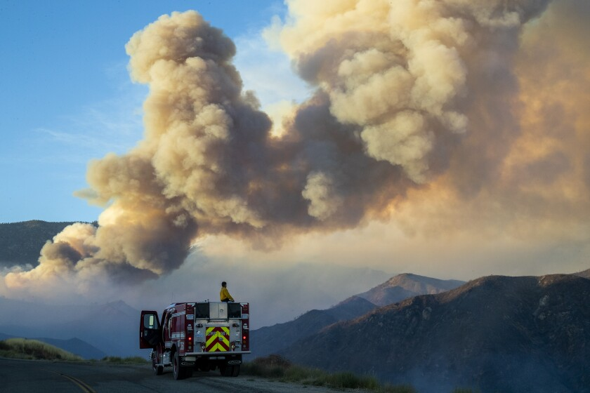 A firefighter looks at a huge plume of smoke from the Apple fire