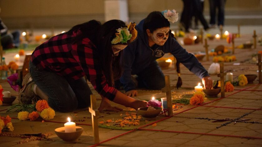 Women wearing calavera makeup associated with Mexico's Day of the Dead holiday build altars for loved ones at the California Center for the Arts, Escondido's annual Dia de los Muertos celebration. This year's event will feature flowers grown in Mexico.