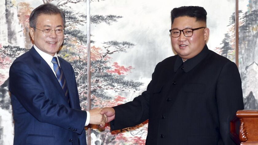 South Korean President Moon Jae-in, left, and North Korean leader Kim Jong Un shake hands after signing documents in Pyongyang.