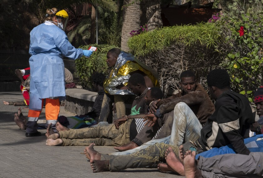 African migrants have their temperature checked because of the coronavirus, after arriving at the coast of Gran Canaria island, Spain on Sunday, Nov. 1, 2020. Crossing the Atlantic Ocean sailing on a wooden boat, a group of 44 migrants arrived at Maspalomas beach. (AP Photo/Javier Bauluz)