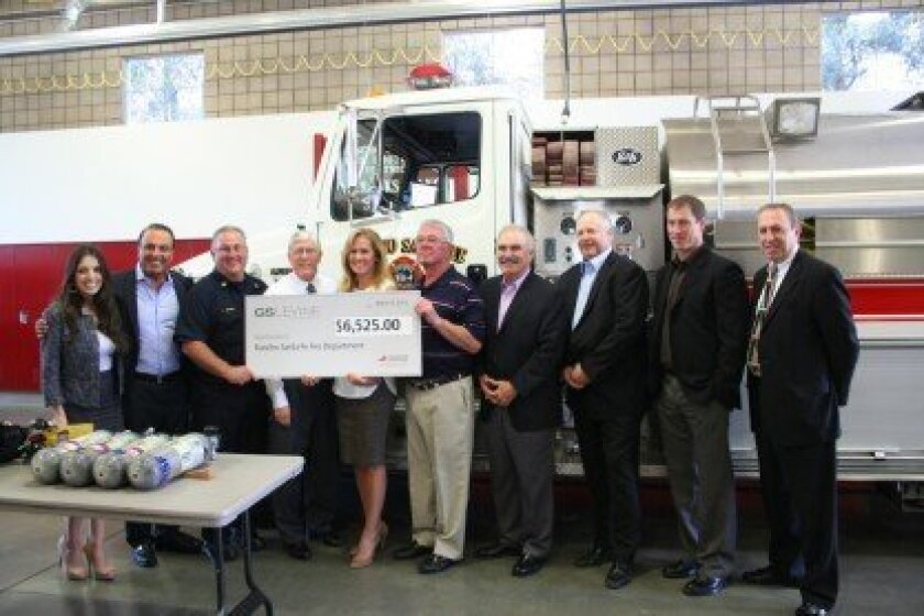 Rancho Santa Fe Fire Chef Tony Michel (third from left) and board members Jim Ashcraft (fourth from left), Nancy Hillgren (fifth from left) and John Tanner (sixth from left) accept a check from G.S. Levine. G.S. Levine was represented by (far left) Alexis Ranglas, Ross Afsahi, (beginning fourth from right, l-r) Rick Avakian, Tom Torgerson, Steve Finley and Larry Sukay. Photo/Karen Billing