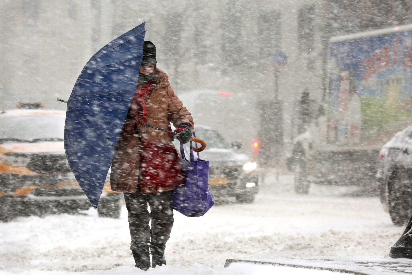 A person walks with an umbrella to block the wind and snow in Manhattan as a winter storm pounds New York on Jan. 4.