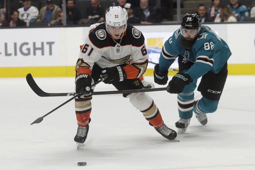 San Jose Sharks defenseman Brent Burns (88) reaches for the puck next to Ducks right wing Troy Terry (61) during the second period on Monday in San Jose.