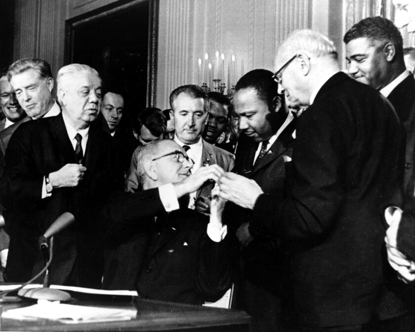President Lyndon B. Johnson reaches to shake hands with Dr. Martin Luther King Jr. after presenting the civil rights leader with one of the 72 pens used to sign the Civil Rights Act in Washington.