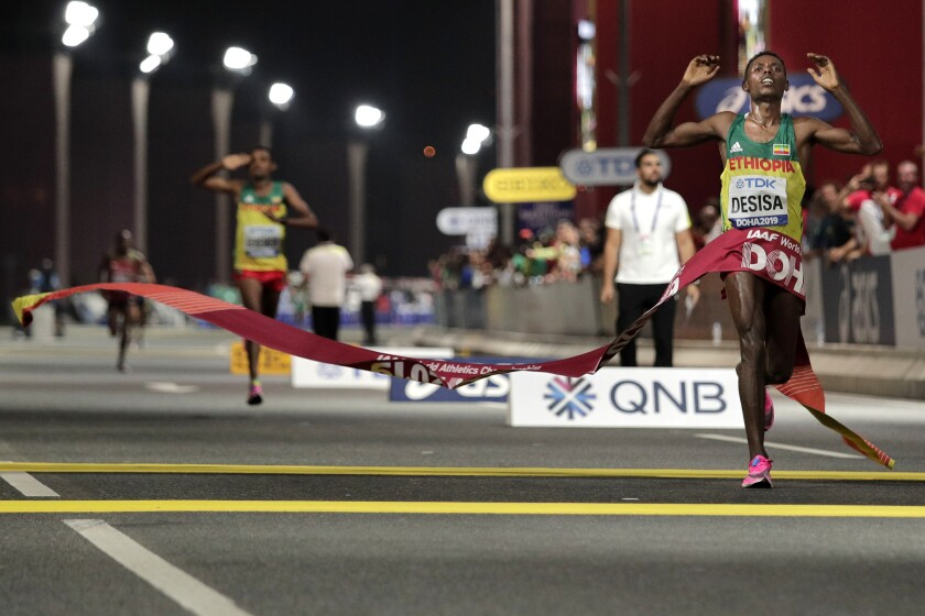 FILE - In this Oct. 6, 2019, file photo, Lelisa Desisa, of Ethiopia, wins the men's marathon at the World Athletics Championships in Doha, Qatar. The IOC is seeking to relocate next summer's Olympic marathon from steamy Tokyo to the cooler northern city of Sapporo after seeing competitors collapse in extreme heat at the world championships in Qatar. (AP Photo/Nariman El-Mofty, File)