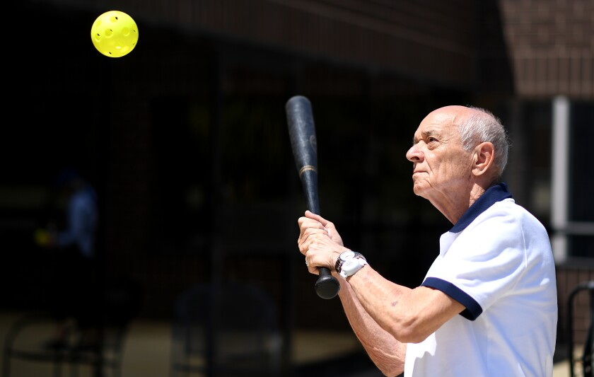 Richard Machinski takes a swing at a wiffle ball during a rooftop game.