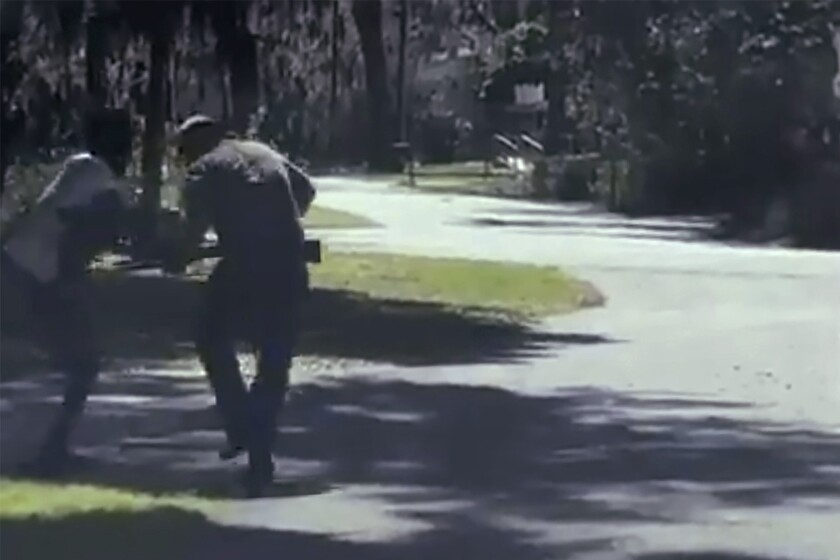ADDS THAT THE AP HAS NOT BEEN ABLE TO VERIFY THE SOURCE OF THE VIDEO - This image from video posted on Twitter Tuesday, May 5, 2020, purports to show Ahmaud Arbery, left, struggling with Travis McMichael over a shotgun on a street in a neighborhood outside Brunswick, Ga., on Feb. 23, 2020. McMichael's father, Gregory, who was also at the scene, said Arbery was shot as the two men fought over the gun, according to the police report. The AP has not been able to verify the source of the video. (Twitter via AP)