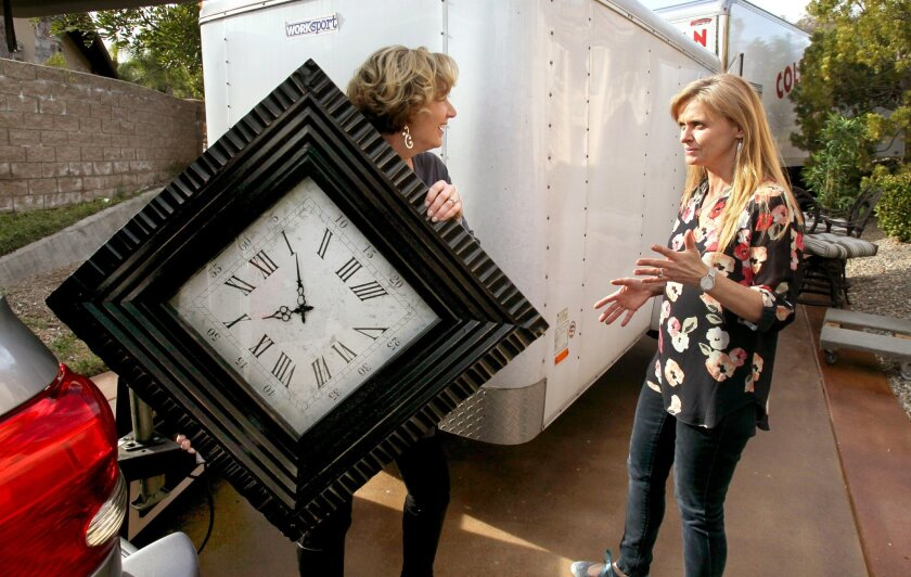 Lisa Gulliver, co-owner of Showhomes, at left, and employee Candy Stokes talk about to where to place a large wall clock in the home the company is staging for sale in an upscale neighborhood of Poway.