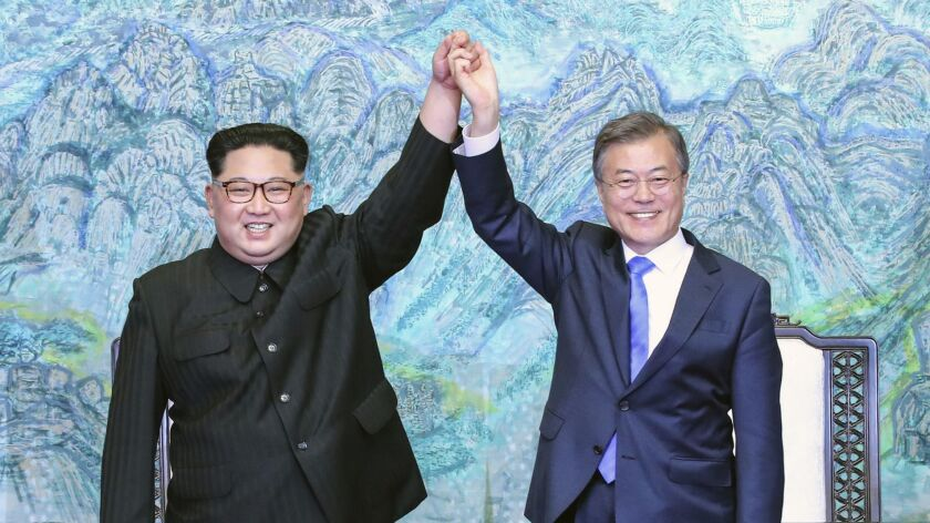 North Korean leader Kim Jong Un, left, and South Korean President Moon Jae-in raise their hands after signing a joint statement at the border village of Panmunjom in the demilitarized zone on April 27, 2018.