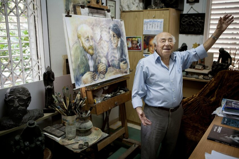 """In this photo taken Tuesday, Nov. 10, 2015, Itzchak Belfer displays his art at his house in Tel Aviv, Israel. With World War II underway and the Nazis closing in, 16-year-old Itzchak Belfer sought the blessing of his father figure to flee his native Poland and head east to Russia. Their brief, but emotional, exchange at the Warsaw orphanage where Belfer was raised ended with the trailblazing educator Janusz Korczak slipping his protégé some money and with tears in his eyes saying """"the chicks are leaving the nest."""" (AP Photo/Dan Balilty)"""