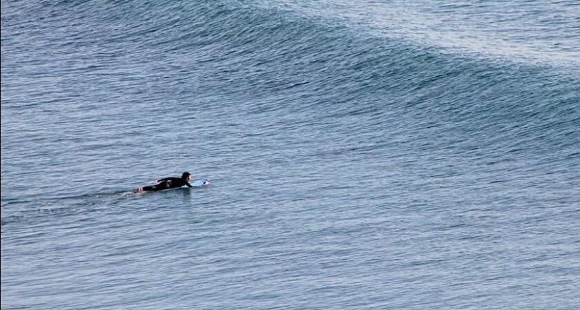 A surfer approaches a wave at Swamis in Encinitas.