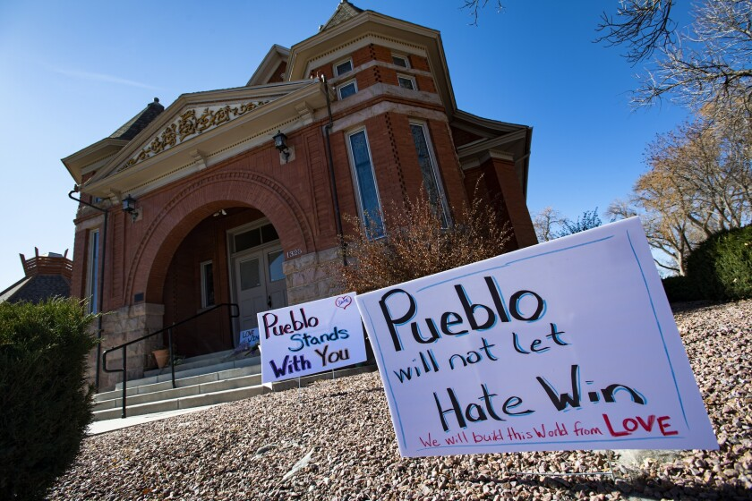 Signs, flowers and candles outside Temple Emanuel in Pueblo, Colo.