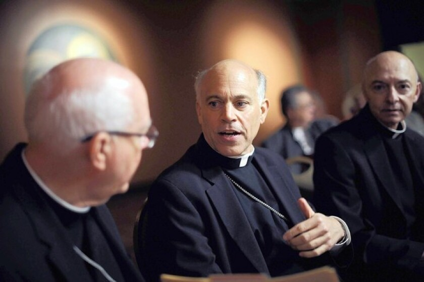 Archbishop Salvatore Cordileone, center, speaks with other clergy members