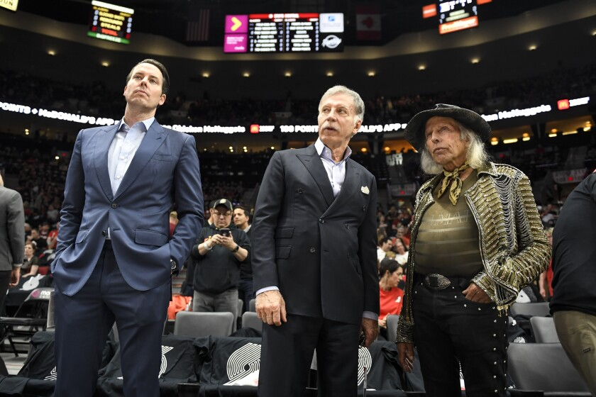 Denver Nuggets president Josh Kroenke stands on the court next to his father, Stan, and NBA fan Jimmy Goldstein