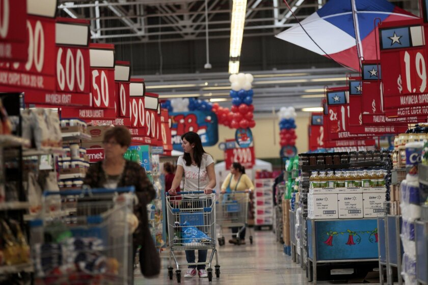 In this Sept. 1, 2015, photo, women shop in a Wal-Mart Lider hypermarket in Santiago, Chile. Soon after Wal-Mart's acquisition of the country's largest supermarket chain Distribucion y Servicio, S.A., Wal-Mart made red the signature color for price signs for its Lider supercenters because Chileans