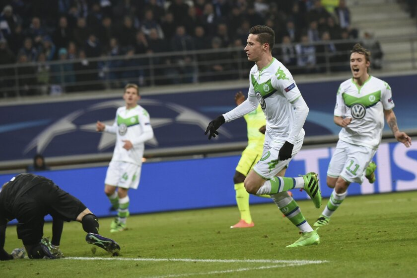 Wolfsburg players start to celebrate as Wolfsburg's Julian Draxler, center, scores his side's first goal passing Gent's goalkeeper Matz Sels, left, during the Champions League round of 16, 1st leg soccer match between Gent and Wolfsburg at Ghelamco Arena in Ghent, Belgium, Wednesday, Feb. 17, 2016.