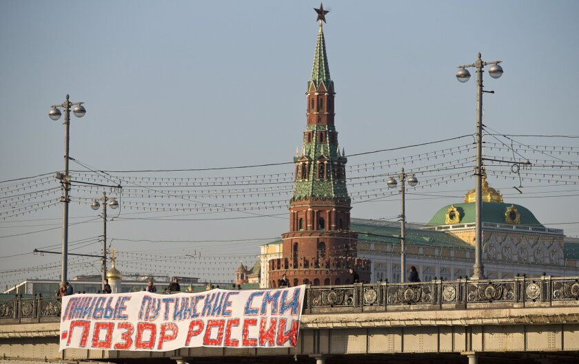 """A banner reading """"Putin's lying media are the shame of Russia"""" hangs from a bridge near the Kremlin on Friday. The Russian government has refused to renew a broadcasting license for Voice of America, adding the U.S.-funded news and cultural programmer to the list of media silenced by the Kremlin."""