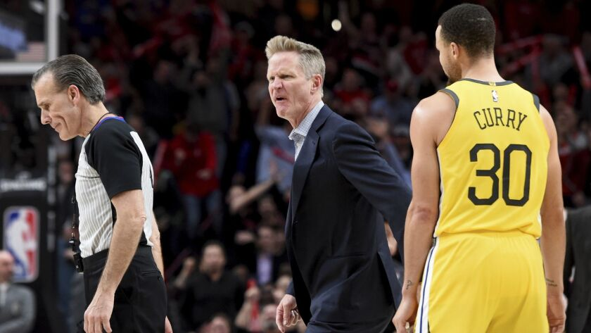 Golden State Warriors coach Steve Kerr, center, yells at referee Ken Mauer, left, after being called for a technical foul, while guard Stephen Curry, right, watches during the second half against the Portland Trail Blazers.