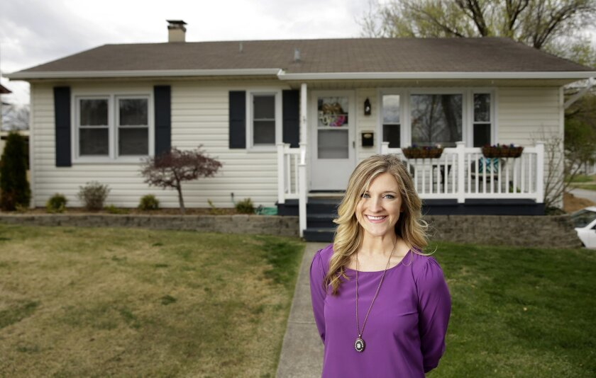 """In this Wednesday, March 30, 2016, photo, Kelsey Funk poses for a photo outside her home in St. Charles, Mo. Funk paid $113,000 for her three-bedroom home in suburban St. Louis about a year ago. """"I think what surprised me was how affordable it is,"""" Funk said. """"My monthly payment is way cheaper than"""