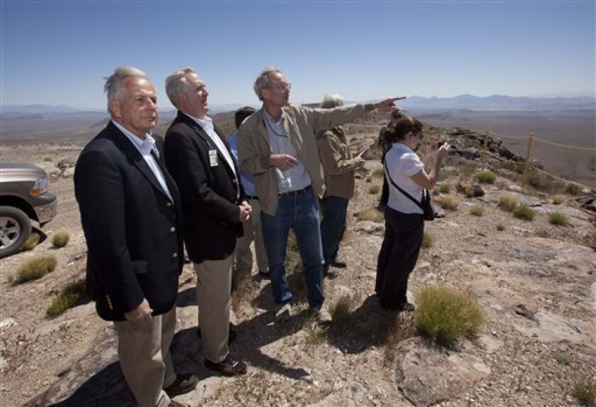 In this photo taken April 26, 2011, Rep. Gene Green, D-Texas, left, and Rep. John Shimkus, R-Illinois, center, listen as Bill Boyle points out landmarks and geologic features from the top of Yucca Mountain in Mercury, Nev. Republicans claim this stark landscape is the nation's best hope for a natio