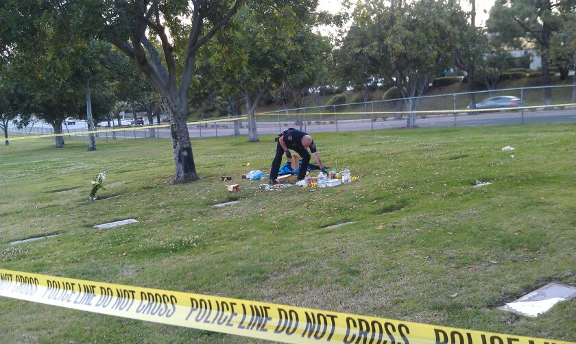 A San Diego Police officer collects evidence at the scene of Saturday's assault at Mount Hope Cemetery.