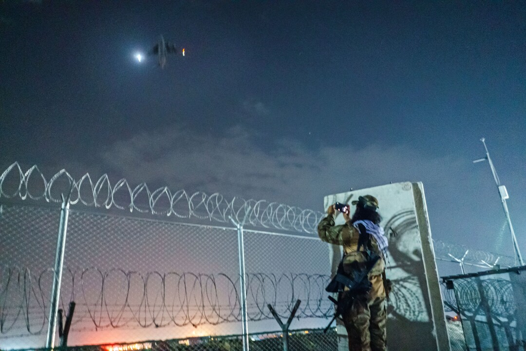 A Taliban fighter takes a picture of a remaining C-17 flight taking off as a farewell memento.