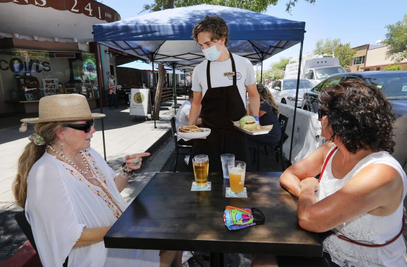 Diners await food in the street dining area in front of Burger Bench on Grand Avenue in downtown Escondido.
