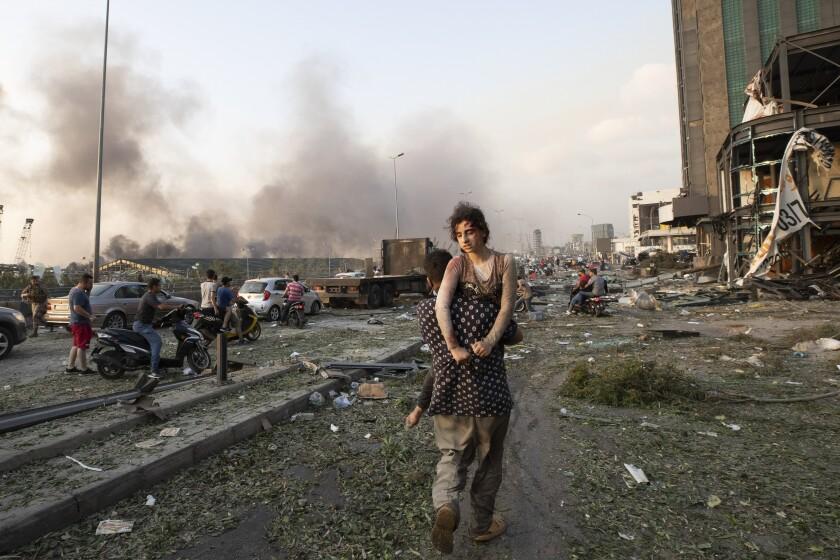 Unas personas evacúan a los heridos luego de una gran explosión en Beirut, Líbano.