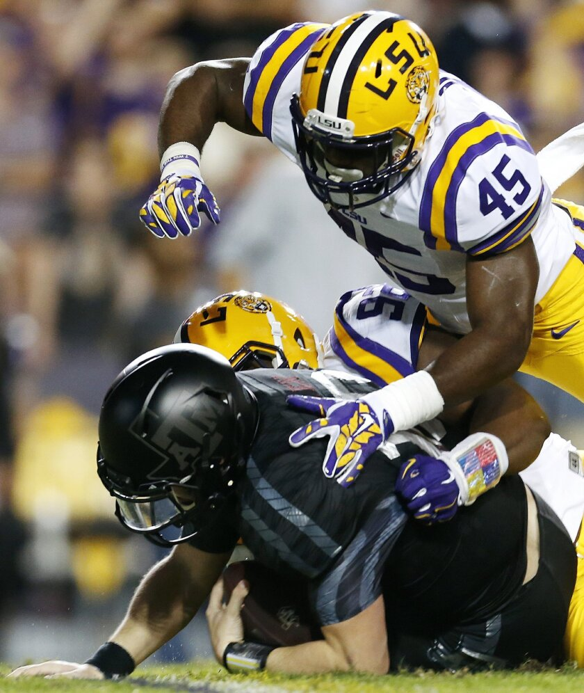 LSU linebacker Deion Jones (45) and defensive end Lewis Neal (92) sack Texas A&M quarterback Kyle Allen (10) during the first half an NCAA college football game in Baton Rouge, La., Saturday, Nov. 28, 2015. (AP Photo/Jonathan Bachman)