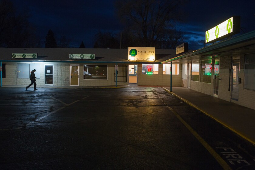 A person walks outside A Wellness Centers marijuana dispensary in Colorado Springs. The dispensary can only sell medicinal marijuana.
