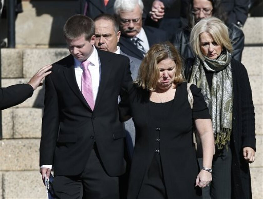 A mourner reaches out to Daniel Ritzer, brother of slain Danvers High School teacher Colleen Ritzer, as he accompanies his mother, Peggie, out of St. Augustine Church in Andover, Mass., Monday Oct. 28, 2013, after Colleen Ritzer's funeral service. Ritzer, 24, who taught math at Danvers High School, was killed in a school bathroom after dismissal Tuesday, police said. Her body was found in woods behind the school, and student Philip Chism, 14, has been arrested in connection with Ritzer's murder.