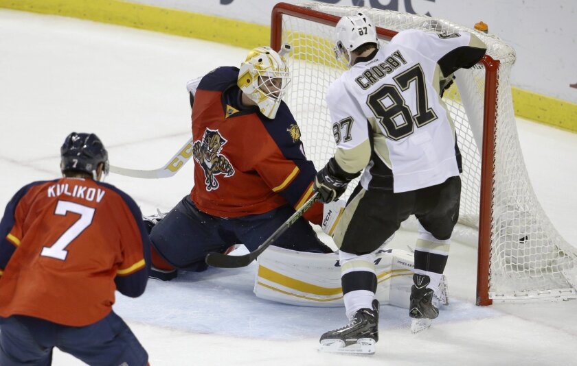 Pittsburgh Penguins center Sidney Crosby (87) scores a goal against Florida Panthers goalie Roberto Luongo, left, to tie the score during the third period of an NHL hockey game, Saturday, Feb. 6, 2016, in Sunrise, Fla. The Penguins defeated the Panthers 3-2 in overtime. (AP Photo/Lynne Sladky)