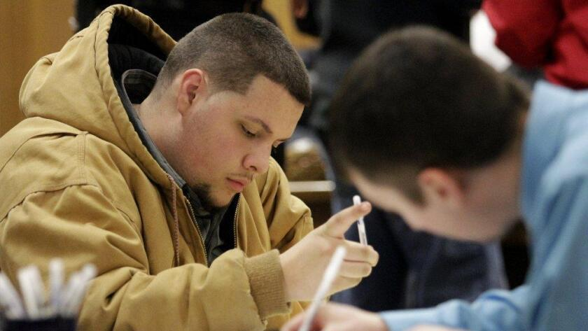Young men fill out job applications in Saginaw, Mich.